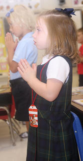 Jenna Mullins, front, and Kelli Jo Johnson open the school year with a prayer in Gina Carter's kindergarten/first grade class.