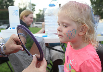 Lilly Ballard, 3, takes a look at her butterfly tattoo in a mirror.
