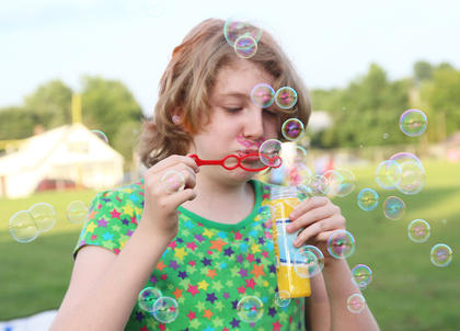 Anna Spalding, 9, blows several bubbles while waiting for the movie to begin.