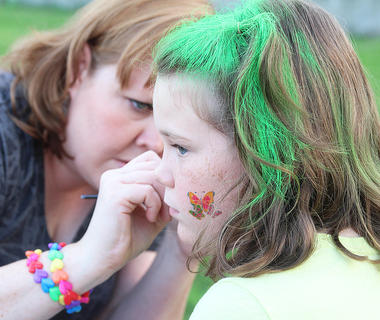 Allison Essex, 10, sits as Library Director Amy Morgeson paints her face.