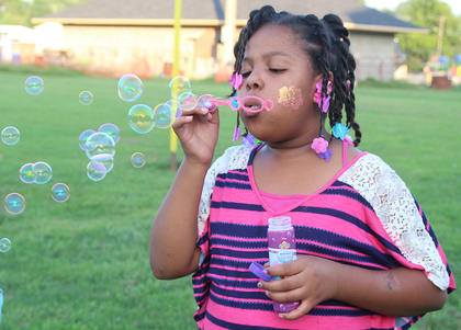 Imyni Means, 8, blows a string of bubbles before the movie starts.