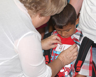 Beverly Thomas places a sticker on Mario Luna's shirt before the bell rings at Lebanon Elementary School.