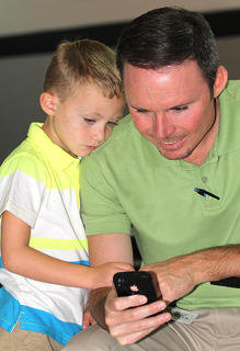 Brad and Cash Bickett kill some time with Dad's cell phone before the starting bell at Lebanon Elementary School.