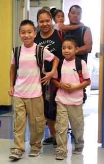 Bryan Flores (fourth grade) leads his family into Glasscock Elementary School to start the school year. He is followed by his brother, Alan (second grade), his mother, Gloria, and his father, Raul, who is carrying his sister, Scarlett (3).