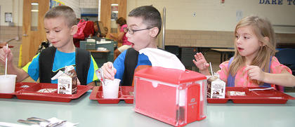 From left, siblings Dalton Dupin (first grade), Evan Dupin (fourth grade) and Sonja Dupin (kindergarten) eat breakfast together on the first day at Glasscock Elementary School.