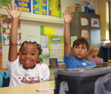 From left, Dominica Cowherd, left, and Lorenzo Venegas raise their hands in Patti Davis' third grade class at Glasscock Elementary.
