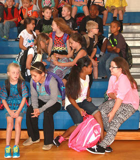 A group of third graders talk in the gymnasium while waiting to go to class on the first day at Glasscock Elementary School.