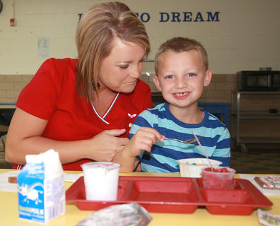 Sabrina Johnson stays to eat breakfast with her son, first-grader Lucas Durham, on the first day at Glasscock Elementary School.