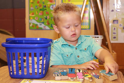 St. Augustine preschooler Brett Mattingly plays with some wooden people to start the school year.