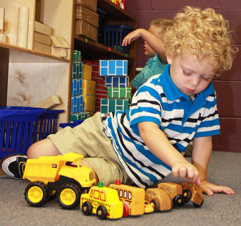 Ethan Mullins plays with some toy trucks on the first day at St. Augustine preschool.