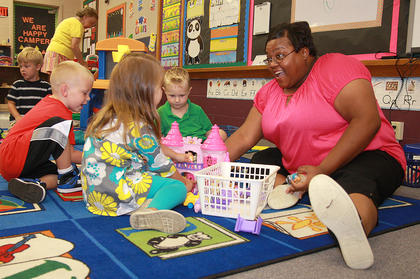 Preschool assistant Laura Furmon jumps right in to play with John Richard Edelen (left), Olivia Gribbins, and Noah Lanz on the first day at St. Augustine.