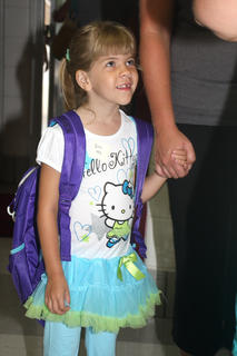 Britney Beaven smiles as she enters the lobby of West Marion Elementary School on the first day of school Wednesday.