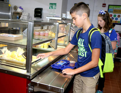 Benjamin Bland and Sidney Click get breakfast on the first day of school at Marion County Middle School.