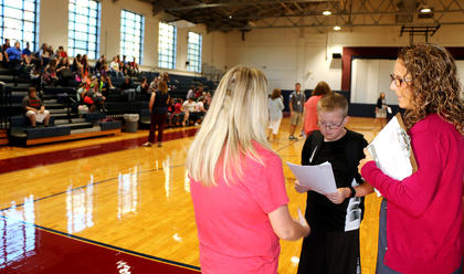 Brandon Estes and his mother, Tammy Washburn, talk to Coury Osbourne, assistant principal/dean of students at Marion County Middle School, on the first day of school.