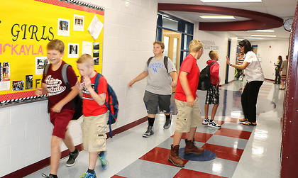 Marion County Middle School Principal Buffy Man gives a student a high five as he walks down the hallway on the first day of school.