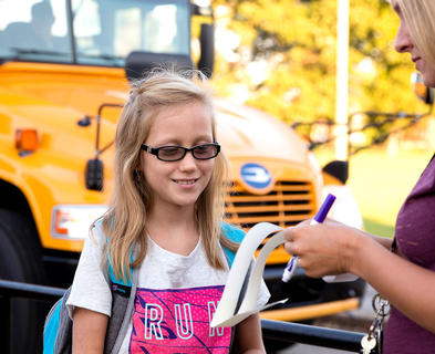 Piper Jones waits to receive a sticker for the bus she will ride home at West Marion Elementary School.