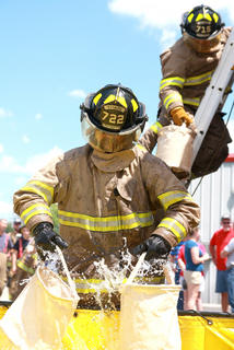John Skaggs of the Raywick Fire Department fills a pair of buckets as Matthew Riggs (partially hidden) passes a bucket to B.J. Thompson (on the ladder).