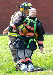 B.J. Thompson of the Raywick Fire Department drags a 200-pound dummy across the finish line in the last leg of the relay challenge.