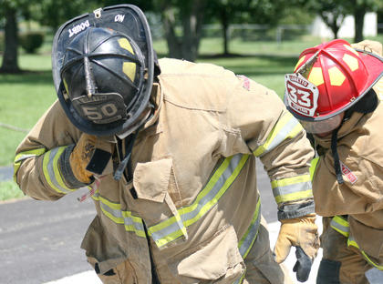 Mike Mullenhour (50) and Keith Willett help the Loretto firefighter team pull a truck.