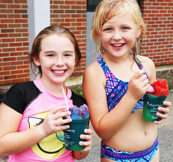 Mary Beth Masterson and Kendall McCandless enjoy snow cones they made together.