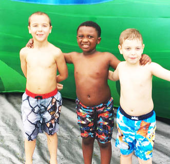 Bryce Wilson, Raylan Marin and Ean Martinez pose for a photo as they wait their turn to race down the giant bouncy slide.