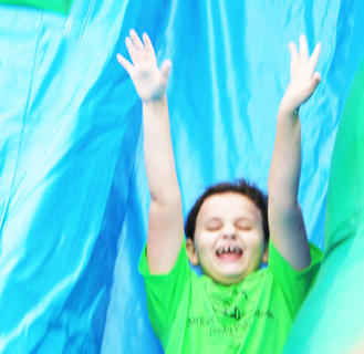 Destiny Gruber puts her hands in the air as she slides down the giant inflatable slide.