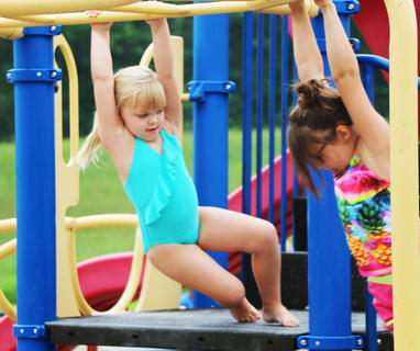 Emma Mattingly and a friend hang around on the monkey bars.