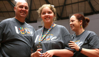 Ryan Graves, 13, of Springfield (center) smiles with her parents, Tracy and Maegen Graves, after receiving her special medallion.