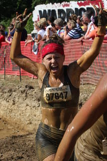 Stevie Lowery celebrates after finishing the Muddy Mayhem obstacle during the Warrior Dash.
