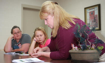 Mary Thompson shows how to make a fairy garden as Madison Wise (center) and Michelle Smothers watch.