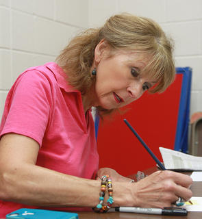Suzanne Turner works on a small watercolor painting.