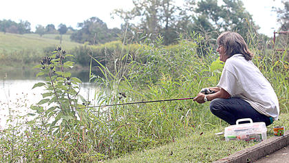 Becky Brown finds a spot to fish on the bank of Badin Pond.