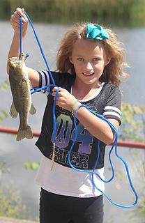 Kimberly Ruffing, 10, poses with a 13-inch largemouth bass.