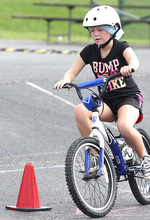 Ava Spalding, 8, shows off her biking skills on the bike safety course Saturday afternoon at Graham Memorial Park.