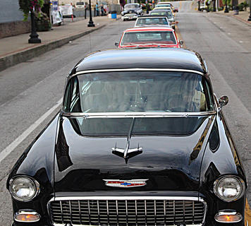 A line of classic cars line up on Main Street to register for the State Farm Insurance, Erica Barnes, Car, Truck and Motorcycle Show.