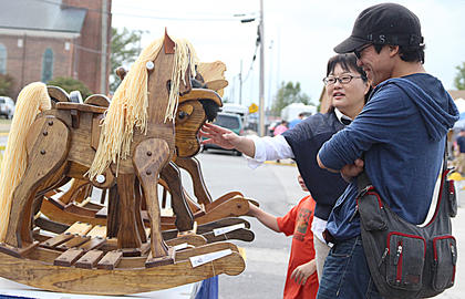 Hatsui Onai, left, and Kazuki Matsuoka are amused by a wooden rocking horse in one of the many arts and crafts booths.