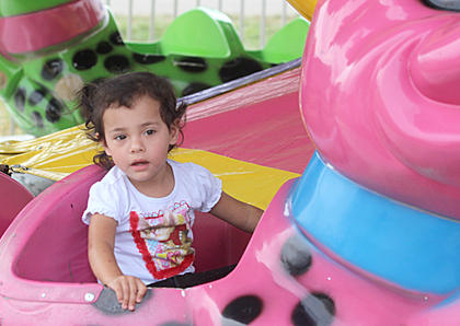 Nelli Ibarra, 2, of Lebanon goes for a ride on a pink alligator.