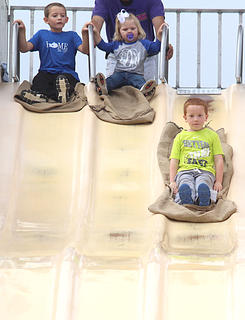 Isaac Wright, 7, and Alexus Spain, 2, watch as Owen Wright, 5, glides down the big slide.
