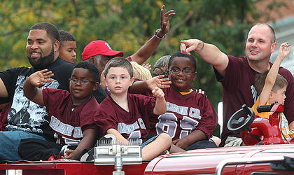 The Marion County Youth Football players and their coaches interact with the crowd from atop a fire truck during the Pigasus Parade.