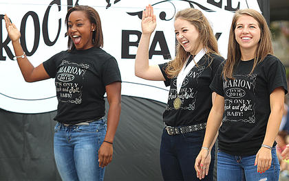 Jarie Newby, Marion County Distinguished Young Woman Adria Whitfill and Rae Mills wave to the crowd while riding on the Marion County Distinguished Young Women float in the Pigasus Parade.