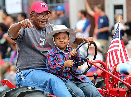 "Carl Alexander lets Montraze ""Bubba"" Churchill take the wheel during the Pigasus Parade."