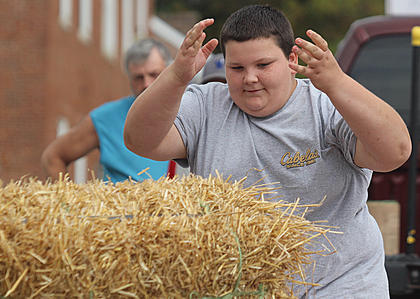 Cody Clark takes a turn in the hay bale toss.