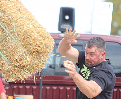 Jake Akers lets go of the hay bale during his winning toss in the men's division.