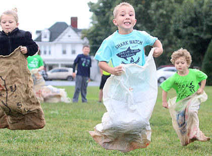 Luke Mattingly, center, takes the lead in the 4-6-year-old sack race. Maci Hutchins is on the left, and Ethan Mullins is on the right.