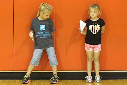 Marley Stout, left, and Maci Hutchins are ready for their turns in the paper airplane throwing contest.