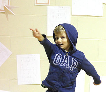 Ben Palagi releases his paper airplane during the kids games Saturday morning at St. Augustine.