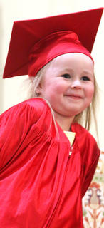 Kennedy Howard, 3, beams as she looks out into the crowd and sees her family during the preschool graduation ceremony at St. Augustine Catholic Church Friday afternoon.