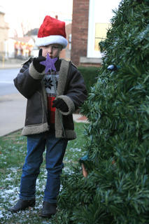 Trey Murphy, 5, examines the magic wand he used to turn on the lights of the Christmas tree outside the Marion County Courthouse at the start of Dickens Christmas festivities.