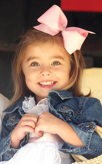 Dyxie Knopp is bright-eyed and all smiles during the Little Miss Ham Days contest Saturday morning.