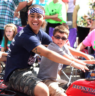 Former Marion County High School Lady Knight and current University of Kentucky Lady Wildcat Makayla Epps drives a four-wheeler during the PIGasus Parade. Riding with Epps is Wyatt Hagan.